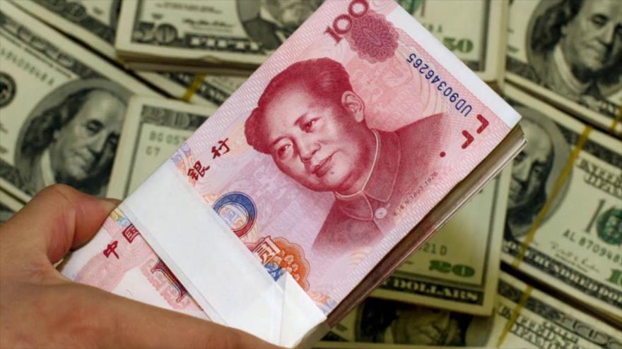 Billetes de yuan, moneda de China delante de billetes de dólares estadounidenses.