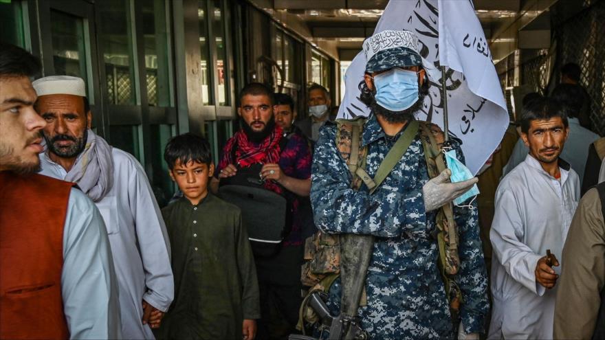 Un talibán hace guardia mientras la gente pasa junto a él en un mercado en Kabul, la capital afgana, 5 de septiembre de 2021. (Foto: AFP)