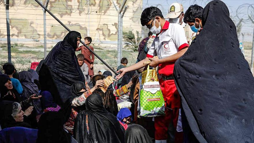 La Media Luna Roja iraní distribuye alimentos a refugiados afganos reunidos en la frontera entre Irán y Afganistán, 19 de agosto de 2021.