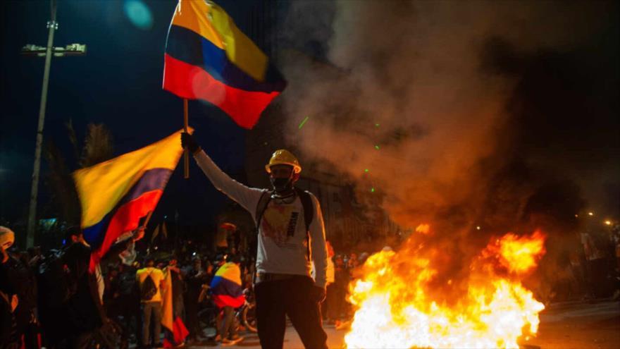 Un colombiano porta dos banderas de su país cerca de unos neumáticos ardiendo, en Bogotá.