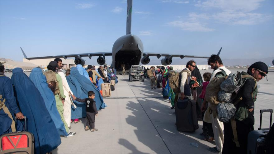 Afganos suben un avión C-17A Globemaster III en Aeropuerto Hamid Karzai de Kabul, capital, 23 de agosto de 2021. (Foto: AFP)