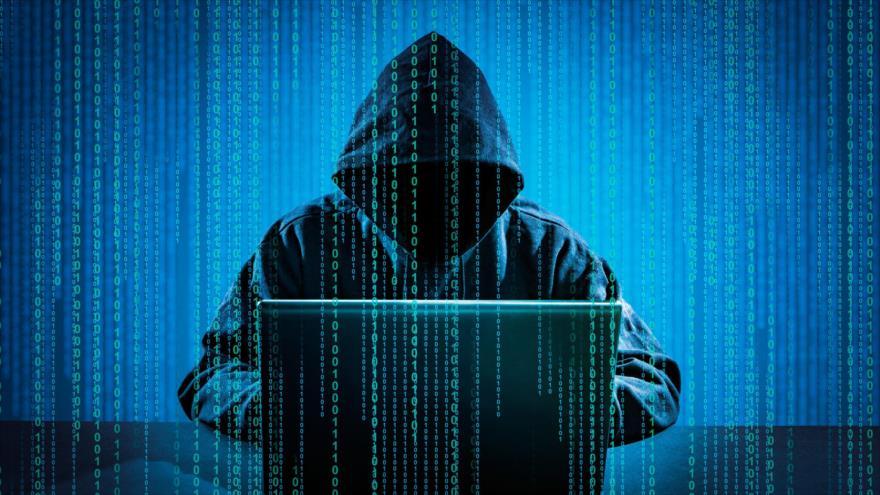 Un encapuchado trabaja con una computadora portátil mientras se proyecta un código cibernético.