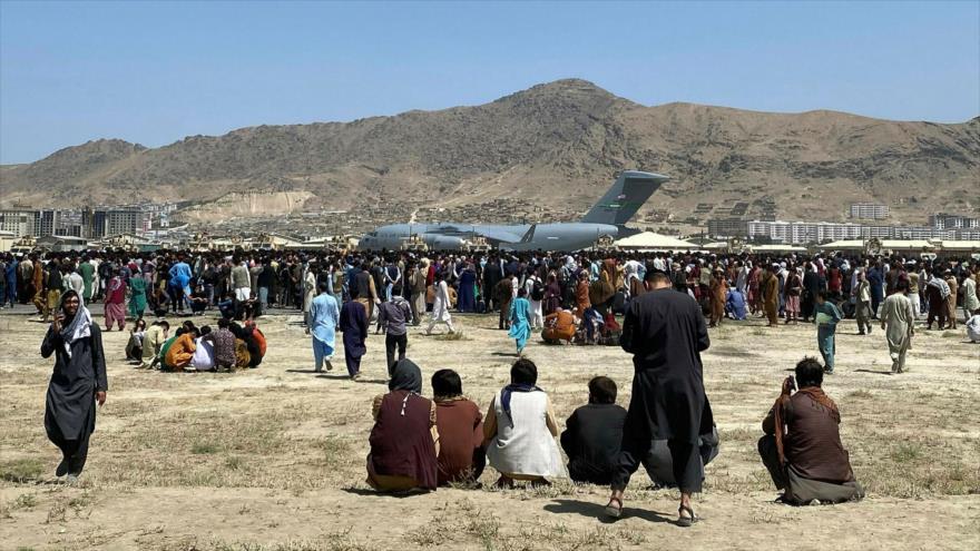 Los afganos se reúnen cerca de un avión de transporte C-17 de la Fuerza Aérea de EE. UU. en el aeropuerto internacional de Kabul, capital afgana.