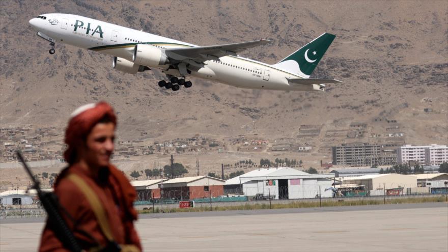 Un combatiente talibán hace guardia mientras un avión paquistaní despega desde el aeropuerto de Kabul, 13 de septiembre de 2021. (Foto: AFP)