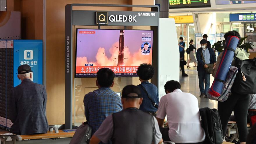 La gente ve una transmisión de noticias de televisión mostrando archivo de una prueba de misiles de Corea del Norte, Seúl, el 15 de septiembre de 2021.( AFP)