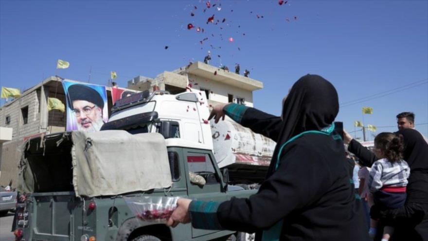 Una mujer libanesa arroja flores cuando un convoy de combustible iraní pasa por su aldea, 16 de septiembre de 2021. (Foto: Reuters)