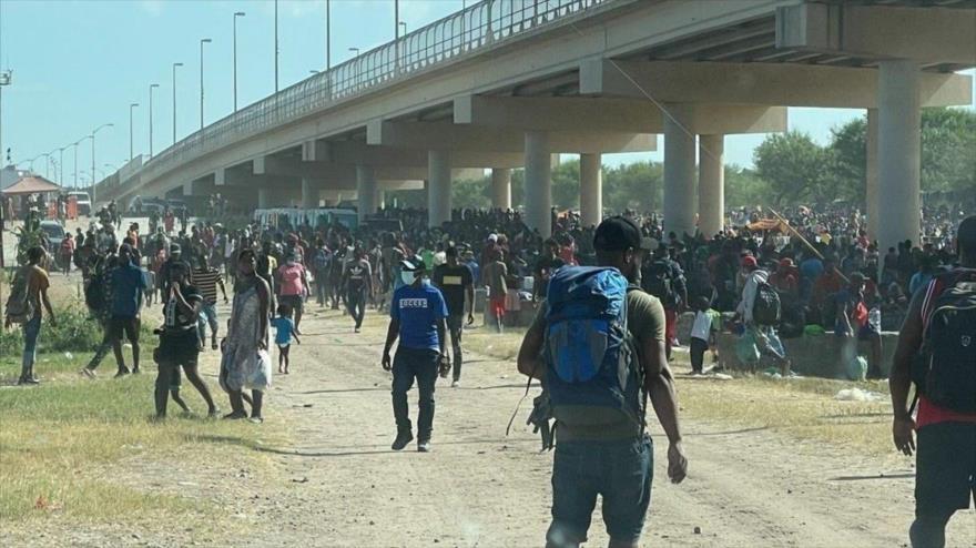 Los migrantes se reúnen bajo el puente internacional de la ciudad Del Río en Texas.