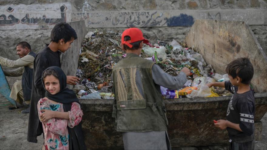 Niños recogen alimentos y materiales reciclables en una basura cerca del aeropuerto de Kabul, Afganistán, 21 de septiembre de 2021. (Foto: AFP)