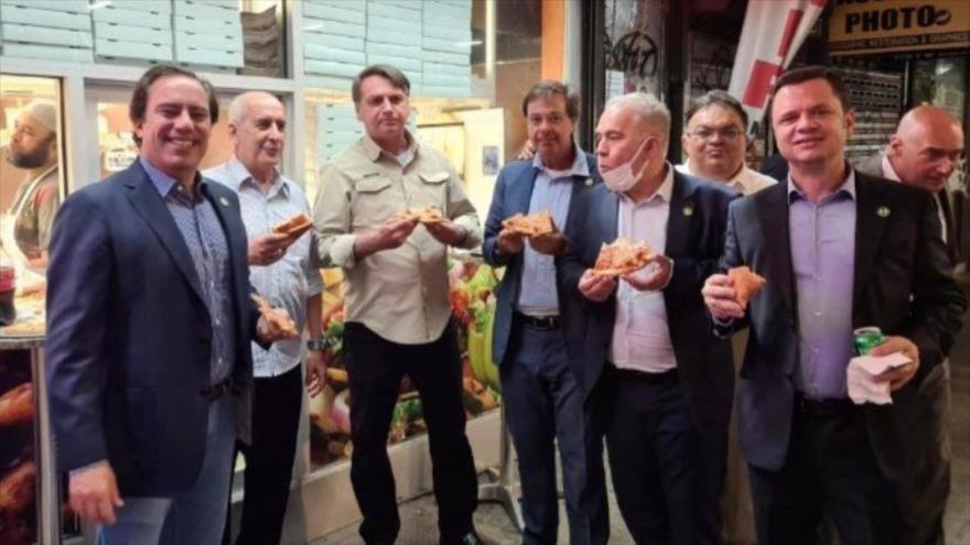 El presidente de Brasil, Jair Bolsonaro (tercero a la izquierda), come pizza junto a ministros en una calle de la ciudad de Nueva York.