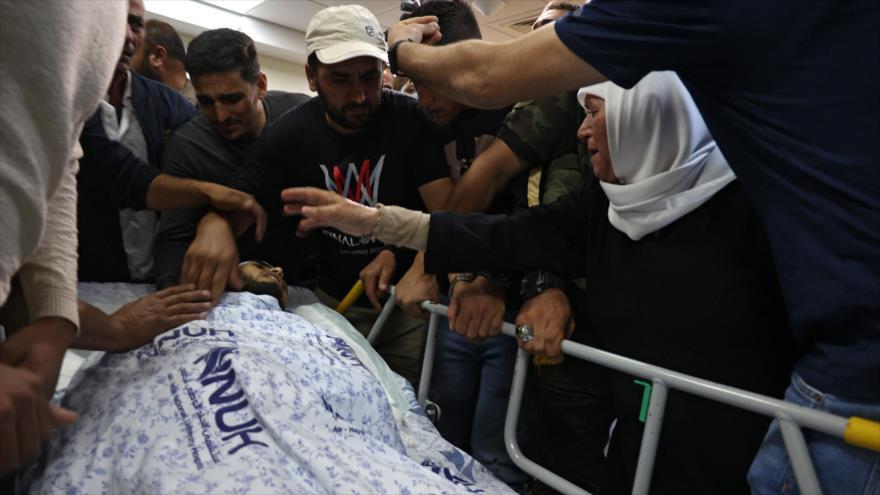 Familiares se reúnen alrededor del cuerpo de Muhamad Ali Jabisa, palestino asesinado por los soldados israelíes, 24 de septiembre de 2021. (Foto: AFP)
