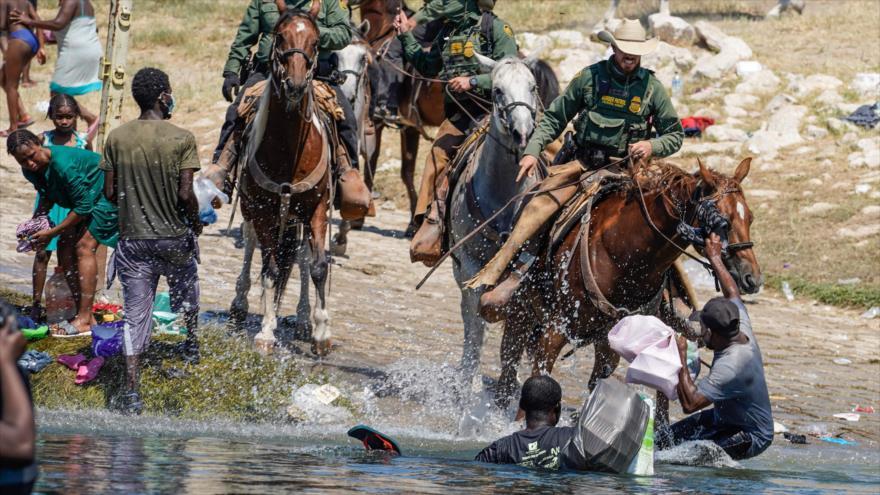 Agentes de la Patrulla Fronteriza de los Estados Unidos a caballo intentan evitar que los migrantes haitianos ingresen a un campamento, 19 septiembre de 2021. (Foto: AFP)