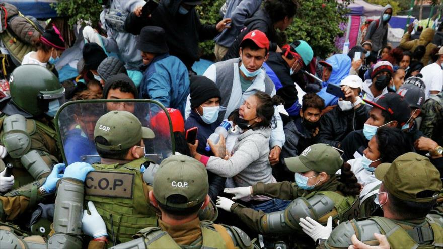 Los carabineros desalojan a migrantes en una plaza de Iquique, al norte de Chile.