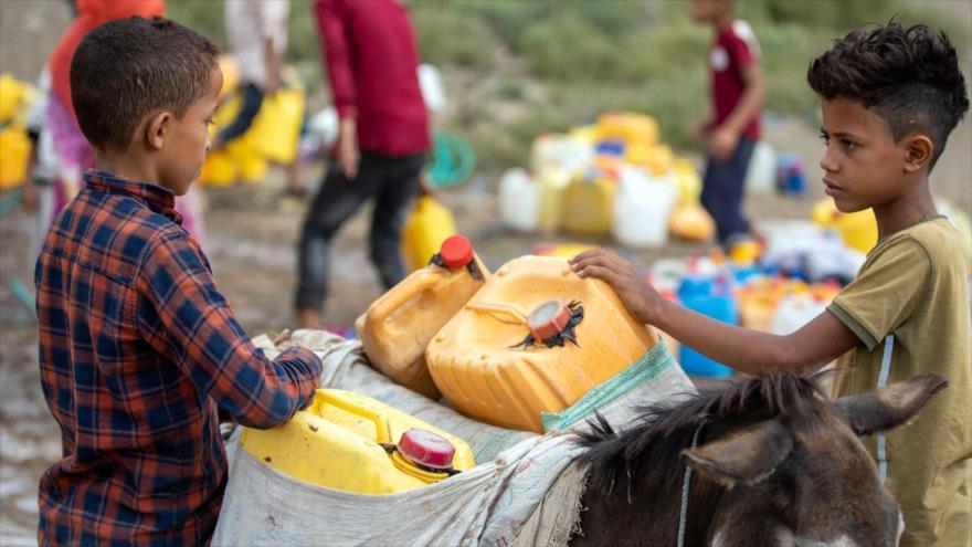 Niños yemeníes transportan agua desde un camión cisterna, a lomos de un burro, en la ciudad de Taiz, suroeste, 26 de agosto de 2021. (Foto: AFP)