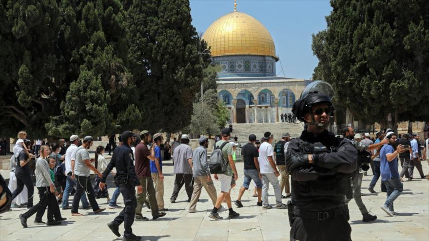 Un oficial israelí monta guardia mientras los colonos visitan la Mezquita de la Cúpula de la Roca en el recinto de la Mezquita Al Aqsa, 18 de julio de 2021. (Foto: AP)