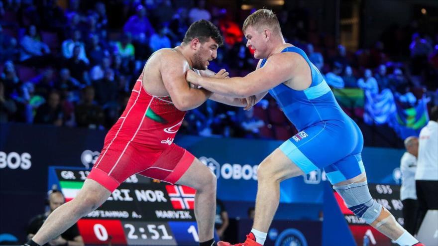 El luchador iraní en la modalidad grecorromana, Ali Akbar Yusei (izda.) compite con su rival el ruso, Zurabi Gedekhauri (dcha.) en el Campeonato Mundial de Lucha de Oslo, capital de Noruega. 9 de octubre de 2021