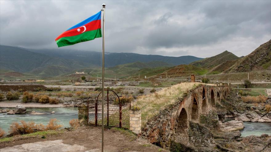 Una bandera nacional de Azerbaiyán ondea junto al puente medieval Jodafarin en la frontera del país con Irán, 9 de diciembre de 2020. (Foto: AFP)