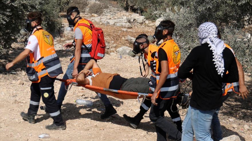 Llevan a un palestino herido por la represión israelí durante protestas en Cisjordania, 8 de octubre de 2021. (Foto: AFP)