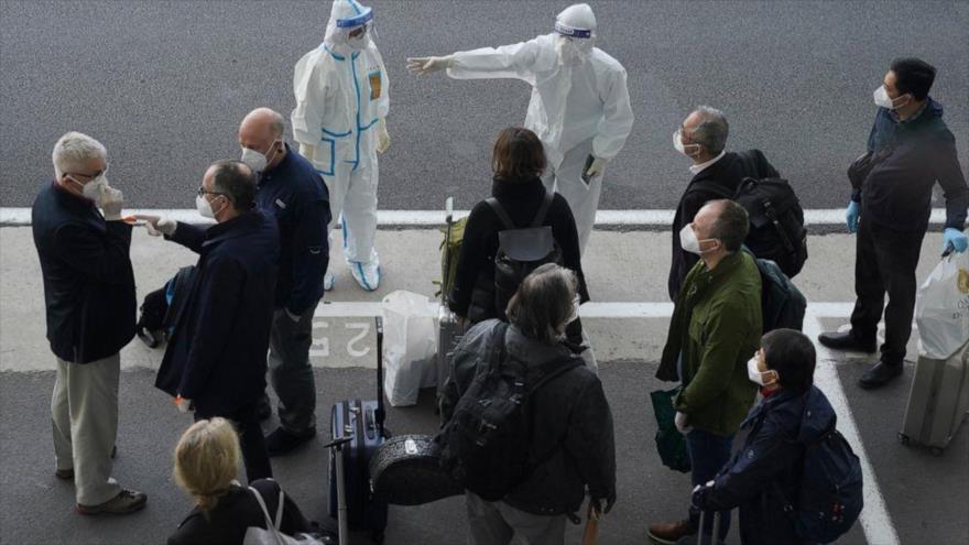 Un trabajador con cubiertas protectoras dirige a los miembros de la OMS tras su llegada al aeropuerto de Wuhan, China, 14 de enero de 2021. (Foto: AP)